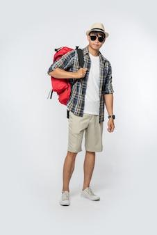 Мужчина в очках отправляется в путешествие, носит шляпу и несет рюкзак