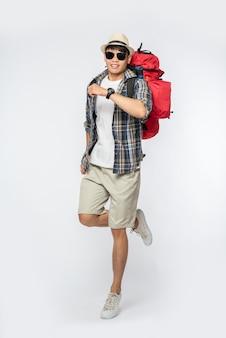 眼鏡をかけている男性が旅行に出かけ、帽子をかぶってバックパックを背負っています