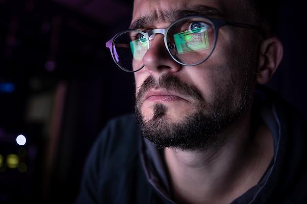 眼鏡をかけている男性は、夜遅くにコンピューターの画面をじっと見つめています。