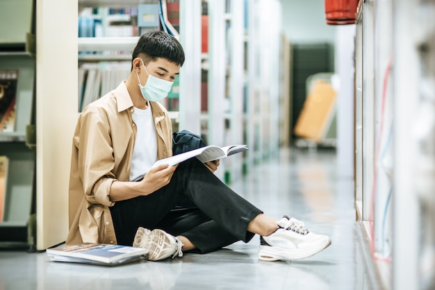 Человек в масках сидит и читает книгу в библиотеке.