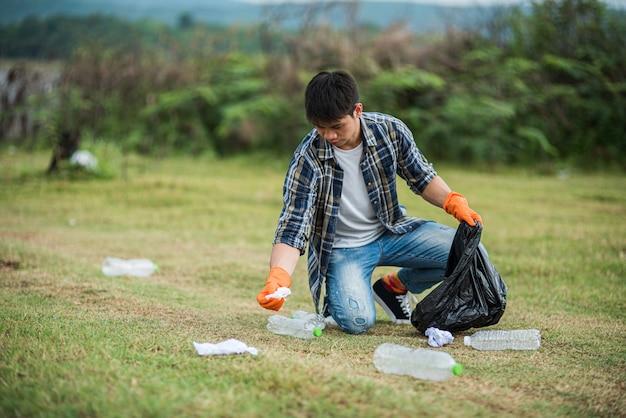 Мужчина в оранжевых перчатках собирает мусор в черной сумке.