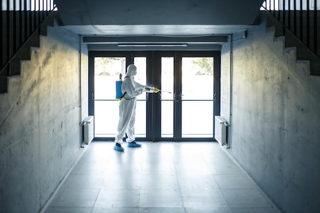 Мужчина в защитном дезинфекционном костюме со спреем стоит перед стеклянной дверью под лестницей. рабочий убирает бизнес-центр. здравоохранение, концепция covid-19.