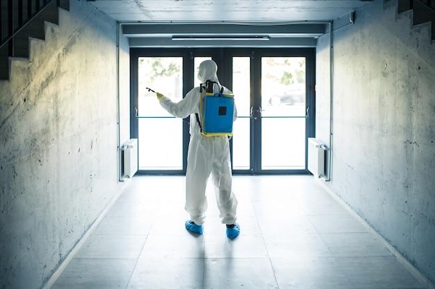 보호 소독 복과 스프레이를 입은 남자가 계단 아래 유리문 앞에 서 있습니다. 비즈니스 센터를 청소하는 노동자. 건강 관리, covid-19 개념.