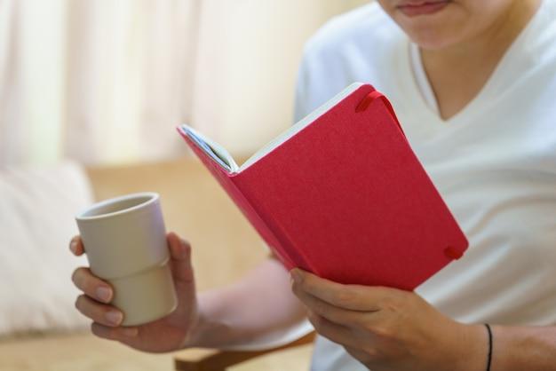 白いtシャツを着て座って本を読み、プラスチック製のコップ1杯のホットコーヒーを持っている男性。