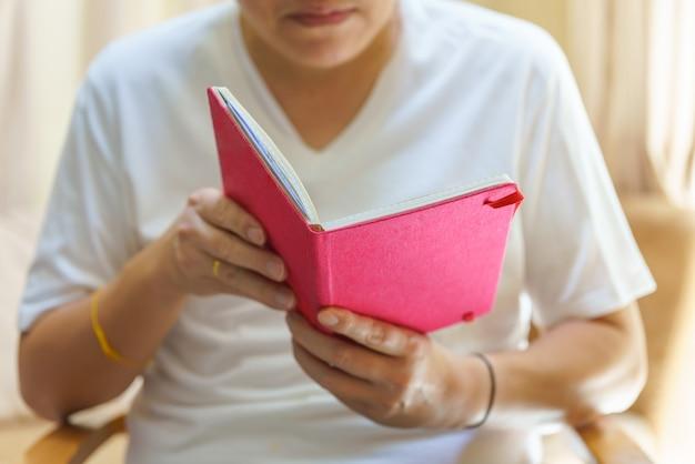 座って本を読んでいる白いtシャツを着た男。