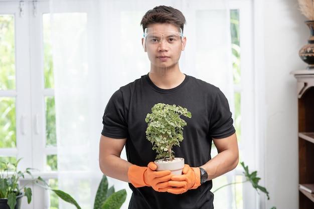 Мужчина носит оранжевые перчатки и стоит, чтобы держать горшок с растением в доме.