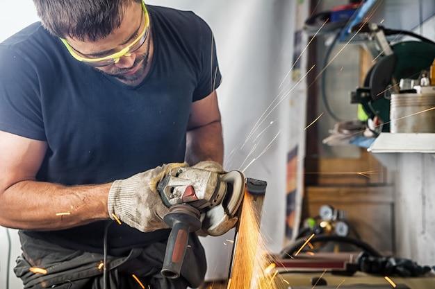 男の溶接工が一生懸命働いて、グラインダー金属とアングル グラインダーを醸造します
