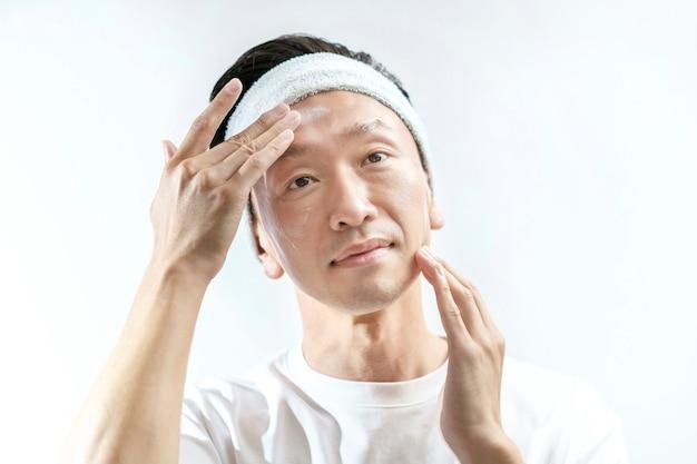 Мужчина, который наносит крем на лицо и белый