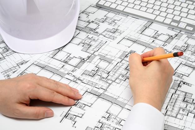 鉛筆を手に持ち、建築図面を描く男