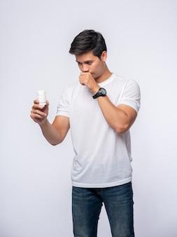 Больной мужчина несет бутылку с лекарством.