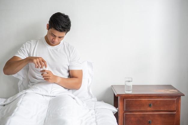 ソファで体調が悪く、抗生物質を服用しようとしている男性。