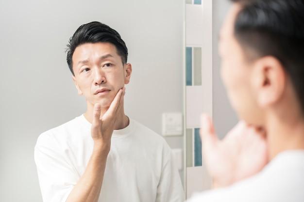 Мужчина, который смотрит в зеркало и проверяет состояние своей кожи