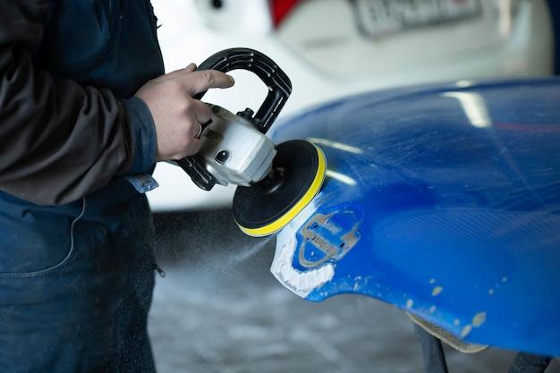 그라인더로 샌딩하고 자동차 서비스에서 자동차 페인트를 준비하는 사람. 수리공 수정 자동차 페인트