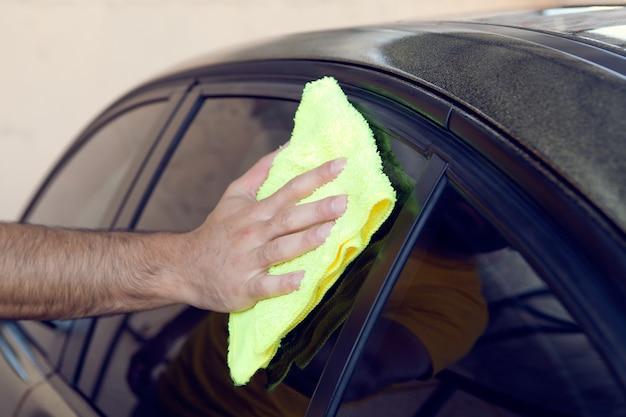 한 남자가 걸레로 차를 닦는다