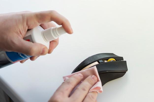 한 남자가 걸레로 더러운 쥐를 닦는다. 컴퓨터 마우스 청소. 알코올 용액 또는 방부제로 미생물을 제거합니다. 코로나바이러스 Covid 19 예방. 디스펜서, 걸레, 천, 살포기, 냅킨 프리미엄 사진