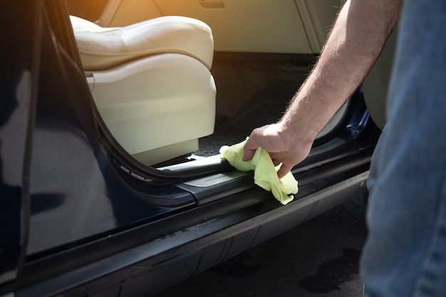 한 남자가 젖은 차를 걸레로 닦는다.