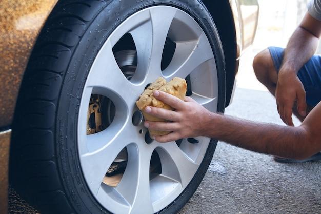한 남자가 스펀지로 바퀴를 닦는다