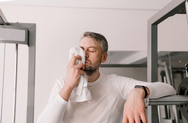 한 남자가 운동 후 수건으로 얼굴의 땀을 닦습니다. 스포츠 홀 강렬한 부하. 심장 운동