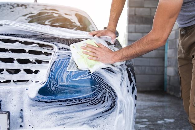 한 남자가 걸레로 차의 거품을 닦습니다. 세차