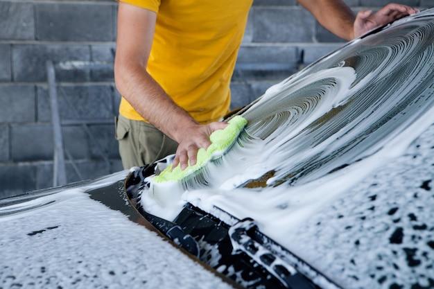 한 남자가 걸레로 차에 묻은 거품을 닦습니다. 세차