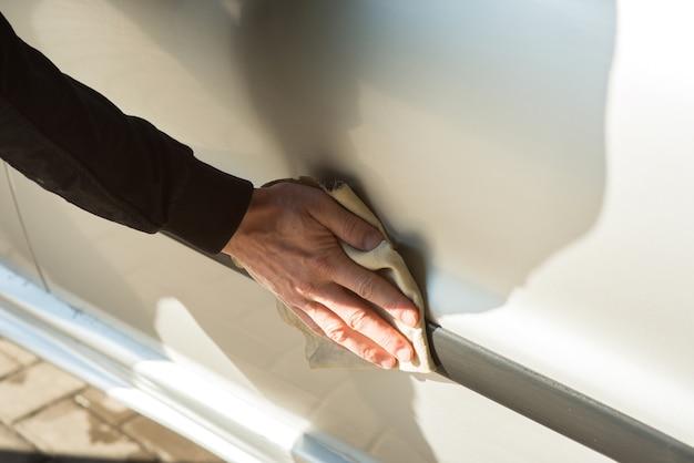 セルフサービスの洗車で車を拭く男性、クローズアップ
