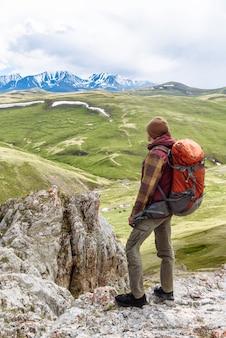 배낭을 메고 산 꼭대기에 있는 관광객이 산의 아름다운 전망을 바라보고 있습니다. 여행 및 휴가 개념