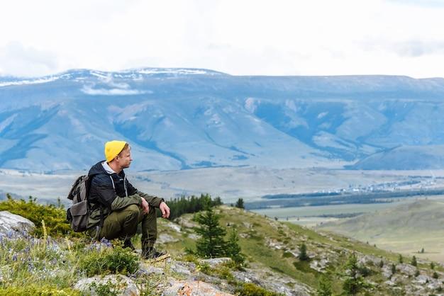 배낭을 메고 관광객이 앉아 산의 경치를 즐깁니다. 여행 및 레저 개념