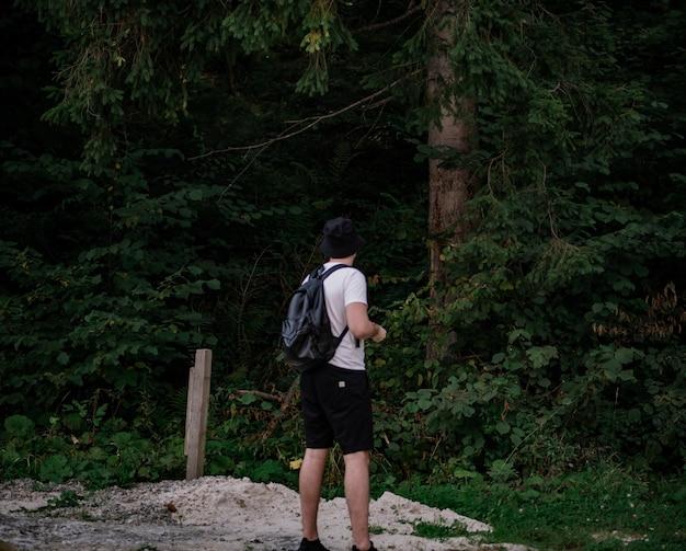 白いtシャツと黒いショートパンツのバックパックを持った男が立って森を見ています