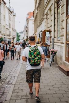 Мужчина с рюкзаком на экскурсии по городу летом.