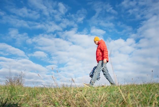 배낭을 든 남자가 녹색 들판을 가로 질러 걷는다.
