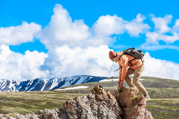 バックパックを背負った男が山の尾根をきれいに歩きます。旅行と野外活動の概念
