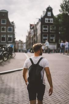 Мужчина с рюкзаком гуляет по улицам амстердама.