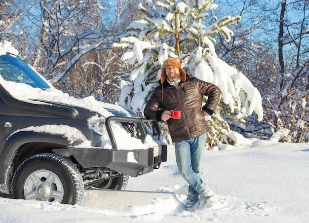 Мужчина с бородой и усами в меховой шапке и куртке в солнечный день в зимнем лесу