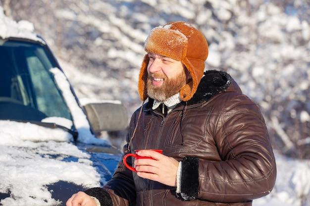 冬の森の晴れた日に毛皮の帽子とジャケットを身に着けているひげと口ひげを持つ男