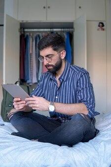 タブレットを使用して彼の寝室のベッドにひげと縞模様のシャツを着た男