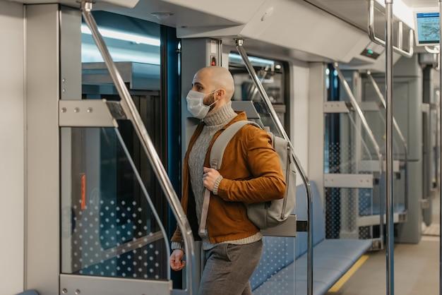 コロナウイルスの蔓延を防ぐためにフェイスマスクにひげを生やした男性が地下鉄の車を離れています。サージカルマスクをかぶったハゲ男が電車の中で社会的距離を保っています。