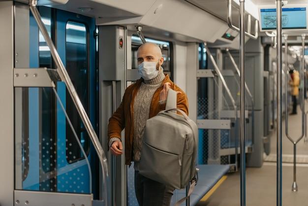 コロナウイルスの蔓延を防ぐためにフェイスマスクにひげを生やした男性が、地下鉄の車に乗っているときにバックパックを背負っています。サージカルマスクをかぶったハゲ男が電車の中で社会的距離を保っています。