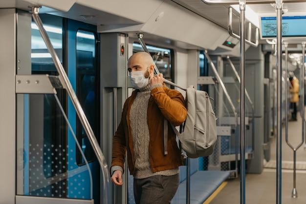 コロナウイルスの蔓延を防ぐためにフェイスマスクにひげを生やした男性が、地下鉄の車に乗っているときに灰色のバックパックを背負っています。サージカルマスクをかぶったハゲ男が電車の中で社会的距離を保っています。