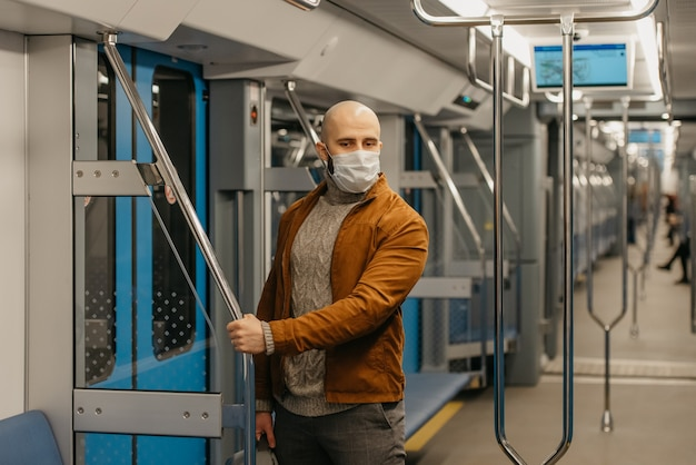 コロナウイルスの蔓延を防ぐために医療用フェイスマスクにひげを生やした男性が、地下鉄の車に手すりを持っています。サージカルマスクをかぶったハゲ男が電車の中で社会的距離を保っています。