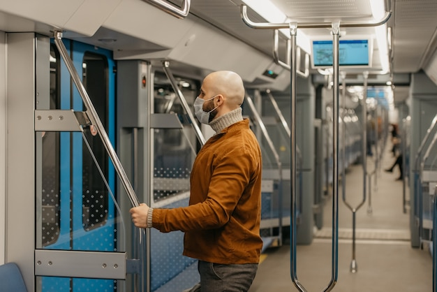 コロナウイルスの蔓延を防ぐために医療用フェイスマスクにひげを生やした男性が、手すりを持って地下鉄の車を離れる準備をしています。マスクをしたハゲ男が電車の中で社会的距離を保っています。