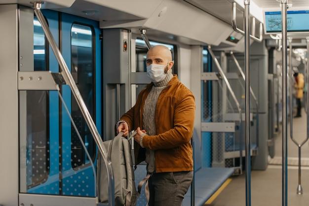 コロナウイルスの蔓延を防ぐために医療用フェイスマスクにひげを生やした男性が、地下鉄の車に乗っているときにバックパックを背負っています。サージカルマスクをかぶったハゲ男が電車の中で社会的距離を保っています。