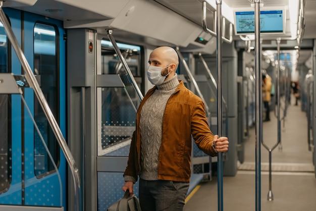 コロナウイルスの蔓延を防ぐために医療用フェイスマスクにひげを生やした男性が、現代の地下鉄の車に乗っています。サージカルマスクをかぶったハゲ男が電車の中で社会的距離を保っています。