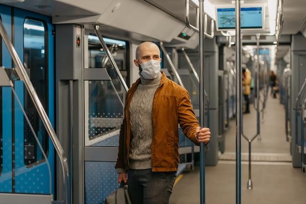 コロナウイルスの蔓延を防ぐために医療用フェイスマスクにひげを生やした男性が、地下鉄の車に乗って手すりを持っています。サージカルマスクをかぶったハゲ男が電車の中で社会的距離を保っています。