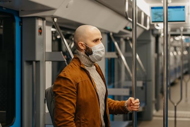 コロナウイルスの蔓延を防ぐために医療用フェイスマスクにひげを生やした男性が立って、地下鉄の車の中で手すりを持っています。サージカルマスクをかぶったハゲ男が電車の中で社会的距離を保っています。