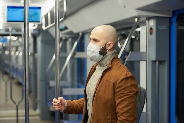 코로나 바이러스 확산을 막기 위해 의료용 마스크를 쓴 수염을 가진 남자가 서서 지하철에서 난간을 잡고 있습니다.
