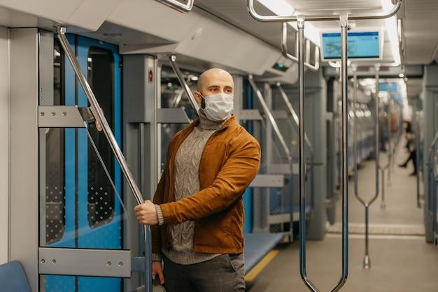 コロナウイルスの蔓延を防ぐために医療用フェイスマスクにひげを生やした男性が横を見つめ、地下鉄の車の中で手すりを持っています。マスクをしたハゲ男が電車の中で社会的距離を保っている