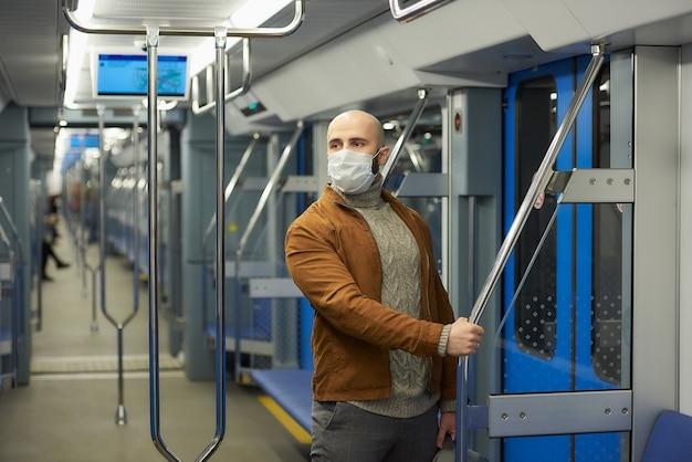 코로나 바이러스 확산을 막기 위해 의료용 마스크를 쓴 수염을 가진 남자가 옆을 쳐다 보며 지하철에서 난간을 잡고있다