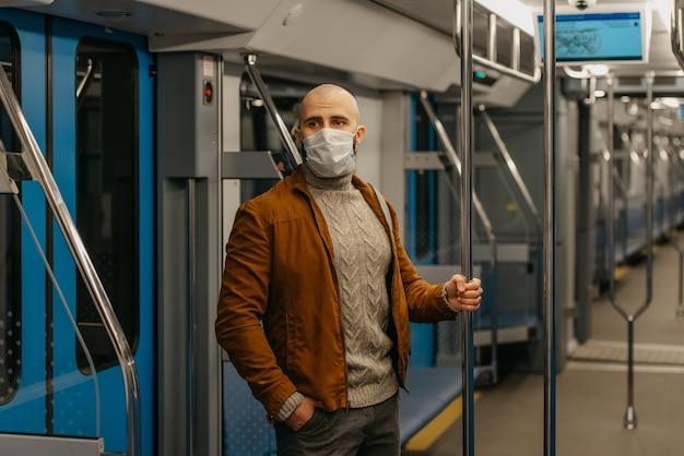 Covid-19の蔓延を防ぐために医療用フェイスマスクにひげを生やした男性が地下鉄の車に乗って手すりを持っています。サージカルマスクをかぶったハゲ男が電車の中で社会的距離を保っています。