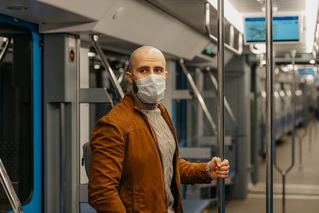 Covid-19の蔓延を防ぐために医療用フェイスマスクにひげを生やした男性が立って、地下鉄の車の中で手すりを持っています。サージカルマスクをかぶったハゲ男が電車の中で社会的距離を保っています。