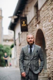 イタリアの灰色のスーツを着たスタイリッシュな男性、シルミオーネの旧市街でネクタイをした厳格な灰色のスリーピーススーツを着たひげを生やした男性。
